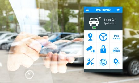 Auto park , pick me up , auto drive and internet of things (iots) in smart car concept. double exposure of hand holding smart phone and application dashboard with blur cars background